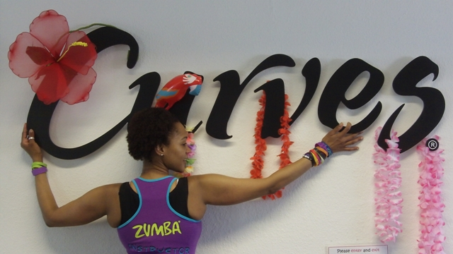Image of Zumba teacher, Ana Sampaio posing under the Curves sign