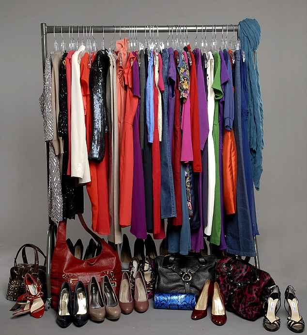 Image of clothes rail with various outfits hanging on it, shoes and bags beneath.