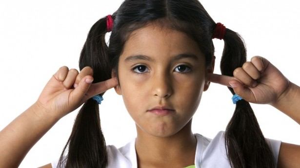Little girl with fingers in ears