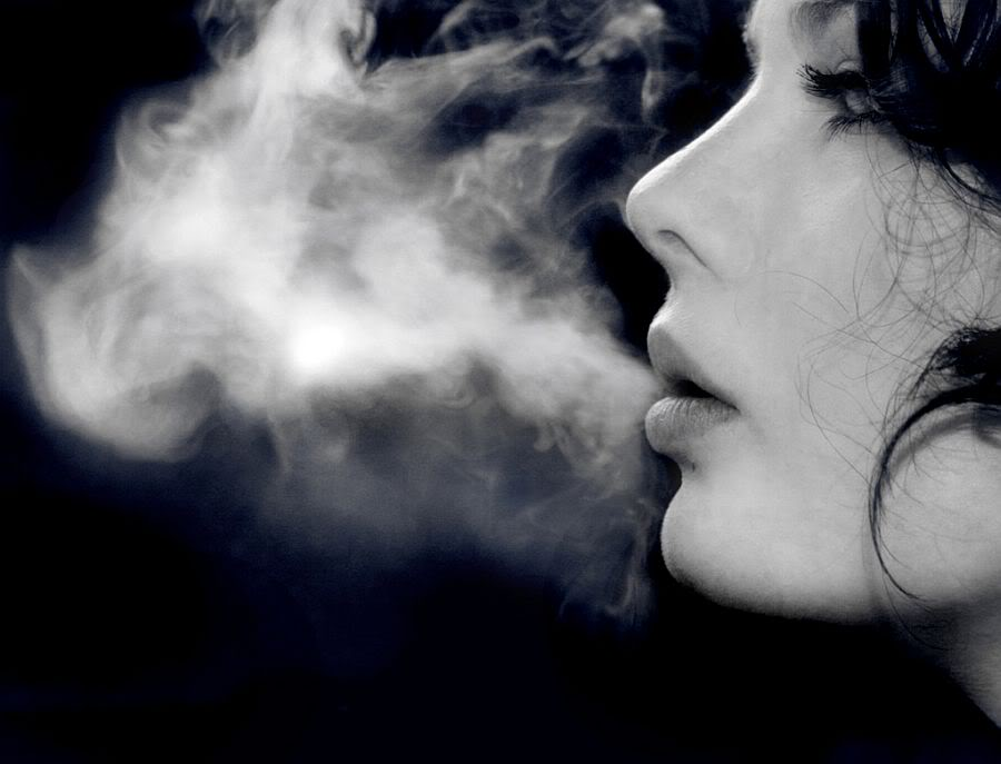 Woman blowing cigarette smoke