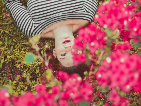 Woman laying in a bed of Spring flowers with stripy top