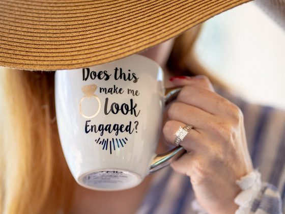 Woman wearing engagement ring and holding cup