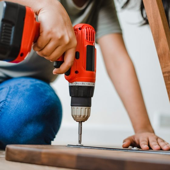 Woman uses drill on wood