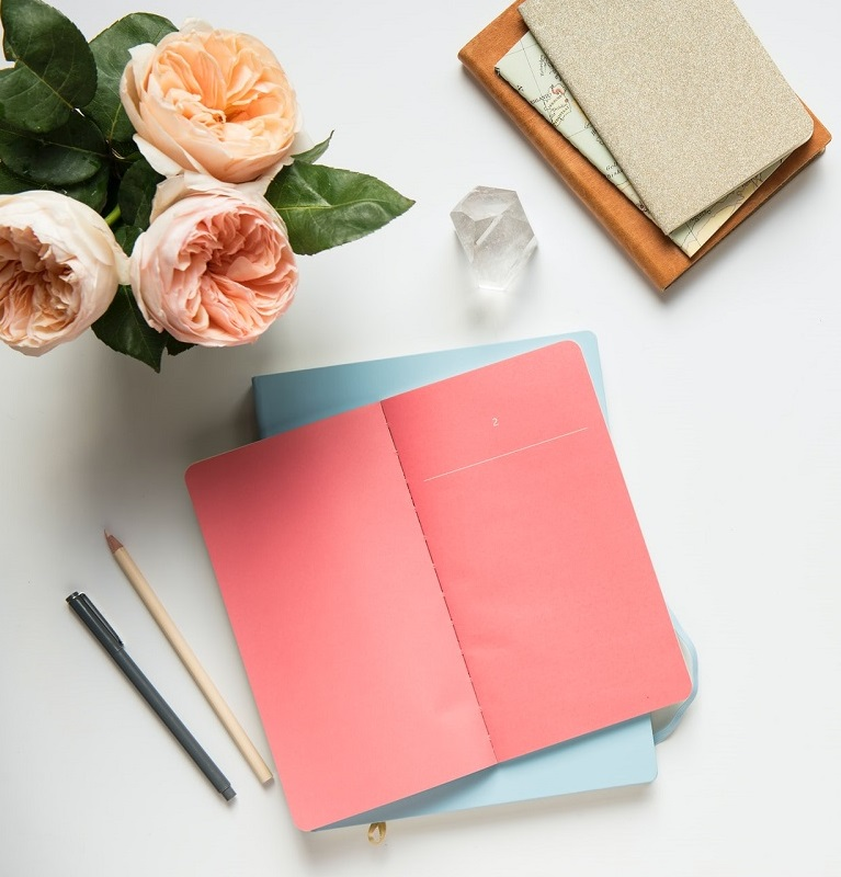 A notebook with pen and flowers. Journaling ideas for mental health