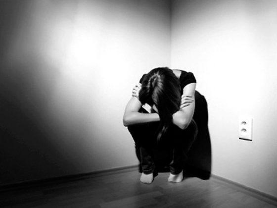 Woman in the corner hugging herself