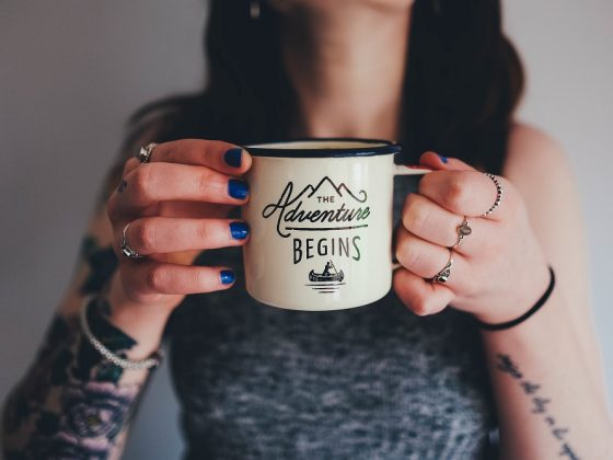 Woman holding a cup with Adventure written on it