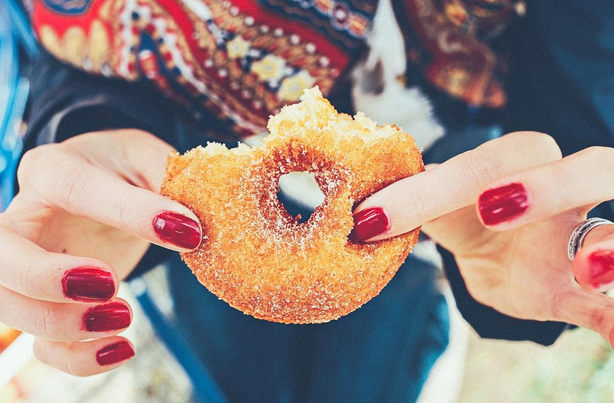 Woman holding sugary doughnut