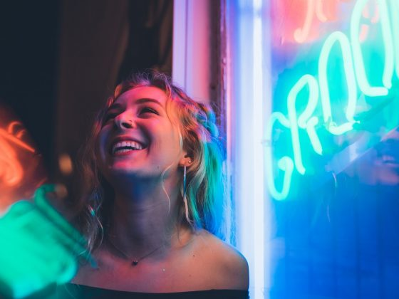 Woman under neon sign laughing